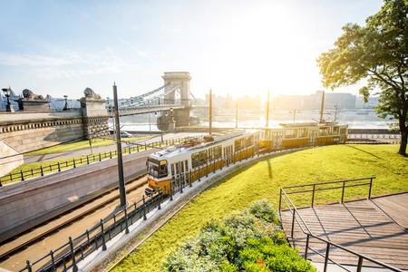 Stadtbildansicht auf der Straßenbahn und der berühmten Kettenbrücke auf dem Hintergrund während des Morgenlichts in der Stadt Budapest, Ungarn