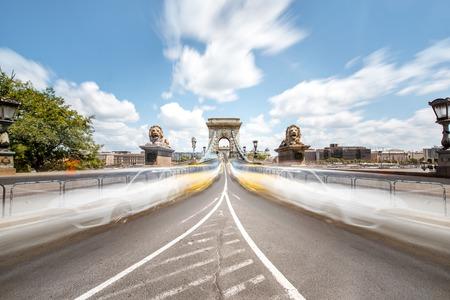 Uitzicht op de weg op de kettingbrug met motie wazig auto's tijdens het daglicht in Boedapest, Hongarije. Afbeeldingstechniek met lange sluitertijd Stockfoto - 105421693