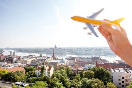 Woman holding toy airplane on the Budapest cityscape background. Flight and air connection in Budapest concept