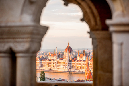 View through the arch on the famous Parliament building during the sunset in Budapest, Hungary