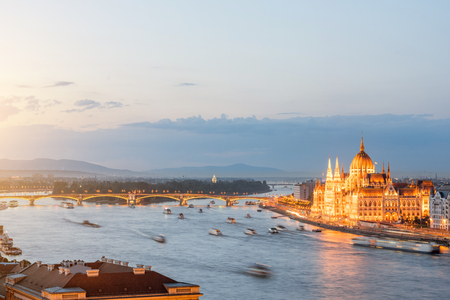 Aerial cityscape view with motion blurred ships and illuminated Parliament building during the twilight in Budapest, Hungary Reklamní fotografie