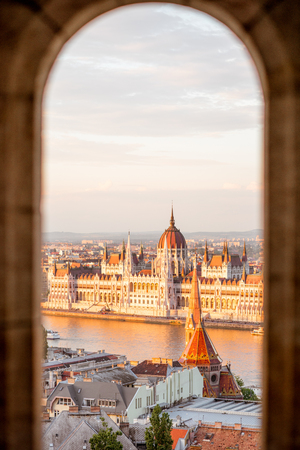 Cityscape view trhough the arch on the famous Parliament building during the sunset light in Budapest, Hungary