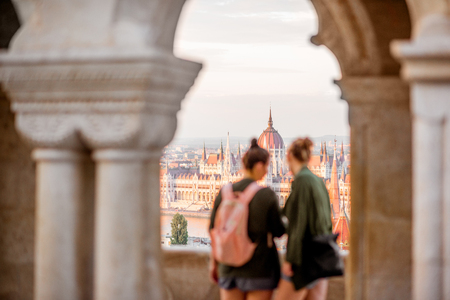 Two women tourists enjoying great view on the Parliament building during the sunset in Budapest. Women are out of focus