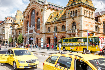 HUNGARY, BUDAPEST - MAY 18, 2018: Street view with yellow taxis, bus and Great Market hall building in Budapest
