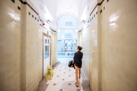 HUNGARY, BUDAPEST - MAY 21, 2018: Interior of the famous Szechenyi medicinal bath with woman walking indoors. This place is the largest bath in Europe with thermal springs