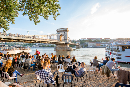 HUNGARY, BUDAPEST - MAY 18, 2018: View on the famous Chain bridge on Danube river with people relax on the riverside during the sunset