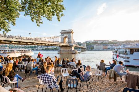 UNGHERIA, BUDAPEST - 18 MAGGIO 2018: Vista sul famoso ponte delle catene sul fiume Danubio con le persone a rilassarsi sulla riva del fiume durante il tramonto