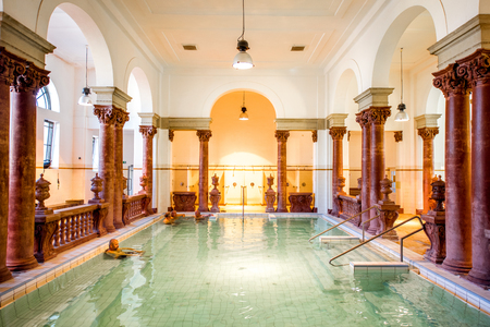 HUNGARY, BUDAPEST - MAY 21, 2018: Interior of the famous Szechenyi medicinal bath with people relaxing indoors. This place is the largest bath in Europe with thermal springs 写真素材 - 105120621