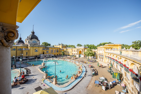 HUNGARY, BUDAPEST - MAY 21, 2018: View on the courtyard of Szechenyi medicinal bath with people relax during the sunny morning. This place is the largest medicinal bath in Europe