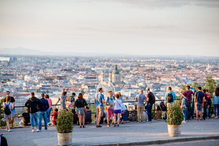 HUNGARY, BUDAPEST - MAY 20, 2018: Tourists enjoying great view on Budapest city standing on the Gellert hill viewpoint during the sunset 스톡 콘텐츠 - 105120655