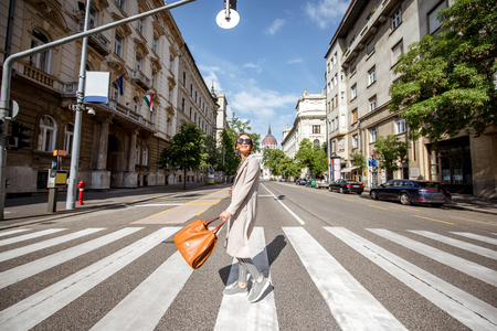 Lifestyle portrait of a woman crossing central street with Parliament building on the background in Budapest city, Hungary Archivio Fotografico