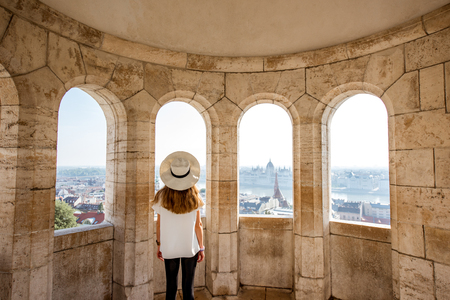 Young woman tourist enjoying cityscape view from the terrace with arches traveling in Budapest, Hungary