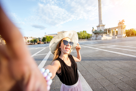 Young woman tourist making selfie photo on the Heroes square traveling in Budapest city, Hungary Stock Photo