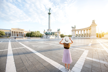 Heroes square with young woman tourist standing back during the morning light in Budapest city, Hungary