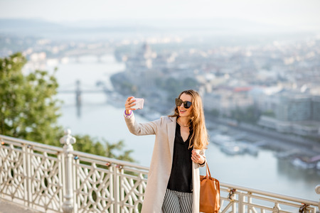 Young woman making selfie photo on the beautiful cityscape background traveling in Budapest city, Hungary