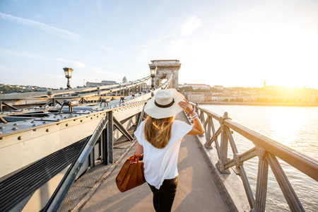 Young woman traveler walking on the famous Chain bridge during the sunset in budapest, Hungary Stock Photo