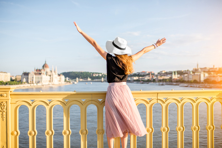 Young woman tourist enjoying landscape view from the Margarete bridge on the Parliament building during the sunset in Budapest city, Hungary