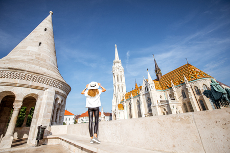 Happy young woman tourist on the Fishermans bastion in fron of the church traveling in Budapest, ungary