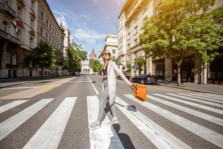 Lifestyle portrait of a woman crossing central street with Parliament building on the background in Budapest city, Hungary Stockfoto - 105233819