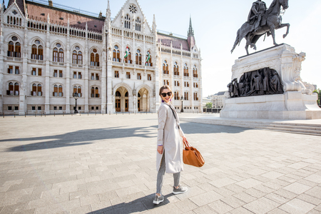 Woman walking on the square near the famous Parliament building during the mornign light in Budapest city, Hungary