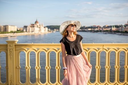 Portrait of a young woman tourist on the Margaret bridge with Parliament building on the background in Budapest, Hungary 版權商用圖片