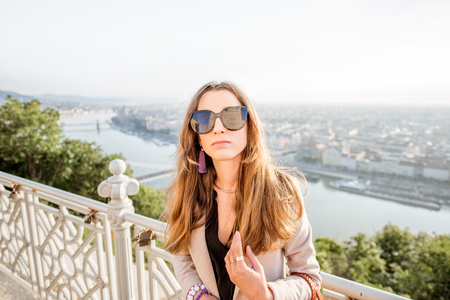 Portrait of a young elegant woman on the beautiful cityscape background traveling in Budapest city