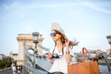 Portrait of a young woman traveler with photo camera and sun hat sitting on the famous Chain bridge in Budapest, Hungary