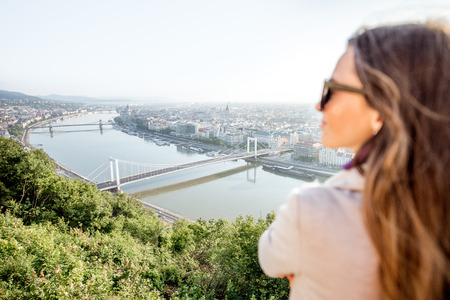Woman enjoying landscape aerial view on the Budapest city during the morning light in Hungary