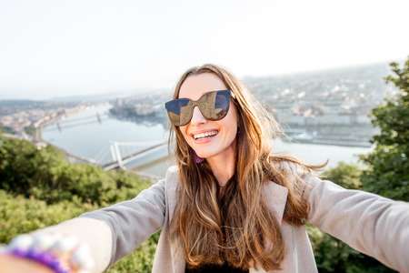Young pretty woman making selfie photo on the beautiful cityscape background in Budapest city, Hungary