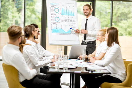Handsome speaker reporting with flip chart during a business conference with partners sitting at the table in the office Stock Photo