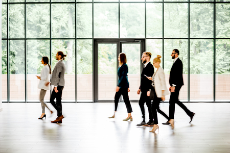 Business people walking at the modern hall on the window background indoors. long exposure image technic with motion blurred people