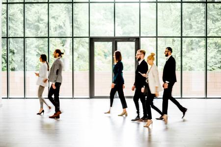 Mensen uit het bedrijfsleven lopen in de moderne hal op de achtergrond van het venster binnenshuis. lange blootstelling beeldtechniek met motie wazige mensen Stockfoto - 104790571
