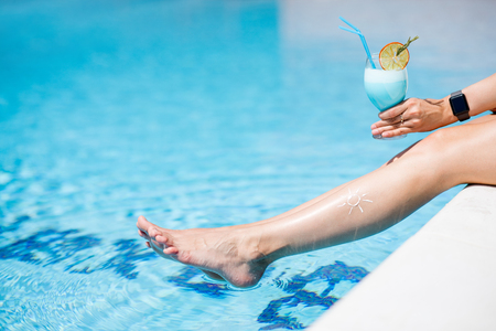 Woman holding summer cocktail on the blue water background relaxing on the poolside outdoors, close-up view Stock Photo