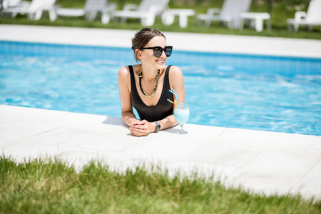 Portrait of a beautiful woman in black swimsuit relaxing with cocktail at the swimming pool outdoors