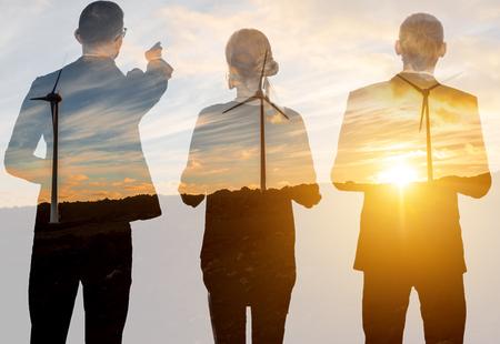 Silhouetten van bedrijfsmensen die tijdens de zonsondergang op de landschapsachtergrond staan met windturbines. Dubbele belichtingstechniek Stockfoto - 105234150