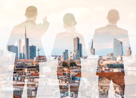 Silhouettes of business people standing back on the modern cityscape background with skyscrapers in Milan. Double exposure image technic