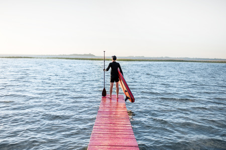 Landscape view on the lake with man standing with paddleboard on the pier during the sunrise Stock Photo