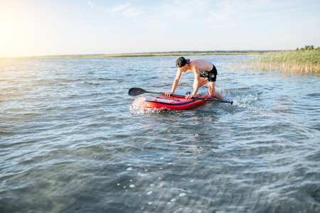 Man jumping on the paddleboard swimming on the lake during the morning light Stock Photo