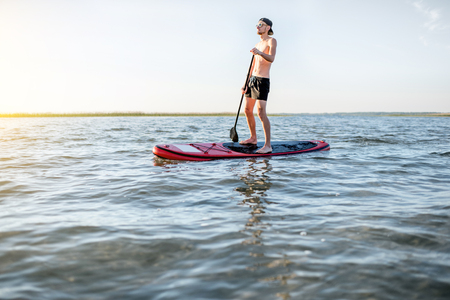 Man paddleboarding on the lake during the morning light Stockfoto