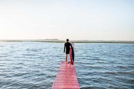 Vue paysage sur le lac avec homme debout avec paddleboard sur la jetée pendant le lever du soleil Banque d'images - 103760142