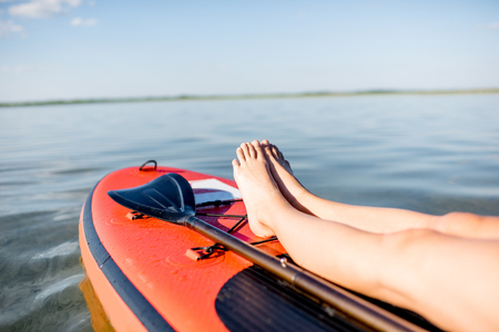 Young woman relaxing on the paddleboard on the lake. Close-up view focused on the womans legs