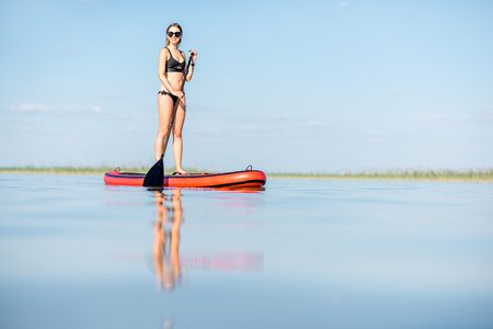 Young woman in black swimsuit paddleboarding on the lake with calm water and beautiful reflection during the sunset