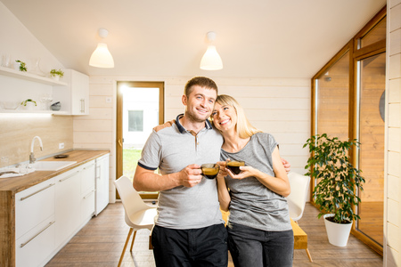 Portrait of a young and happy couple standing together with coffee at the dining room of the modern wooden country house Stock Photo