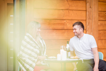 Lovely couple during a romantic dinner on the terrace of their wooden country house