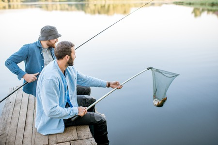 Two friends catching fish with fishing net and rod sitting on the wooden pier at the lake