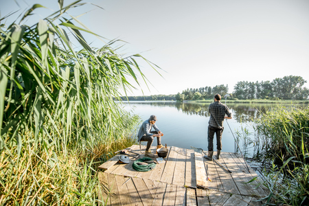 Two fishermen relaxing during the picnic on the beautiful wooden pier with green reed on the lake in the morning