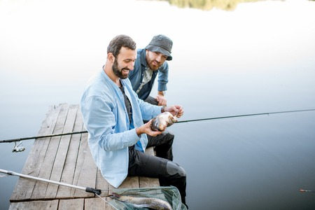 Two happy fishermen holding caught fish sitting on the wooden pier during the fishing on the lake at the morning