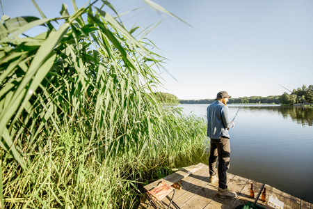 Landscape view on the beautiful lake and green reeds with two men fishing on the wooden pier during the morning light Banque d'images - 106741144