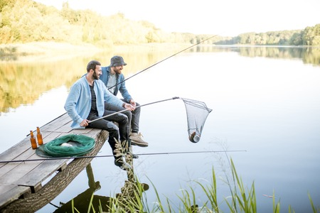 Twee vrienden vangen vis met visnet en hengel zittend op de houten pier aan het meer