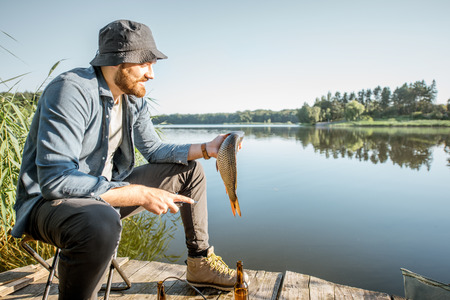 Portrait of a handsome fisherman with fish on the wooden pier near the lake in the morning